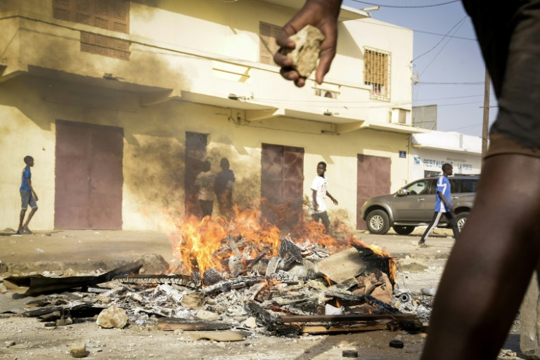 Un manifestant tient une pierre dans une rue de Dakar, le 3 mars 2021, lor de manifestations après l'arrestation de l'opposant sénégalais Ousmane Sonko, visé par une plainte pour viol