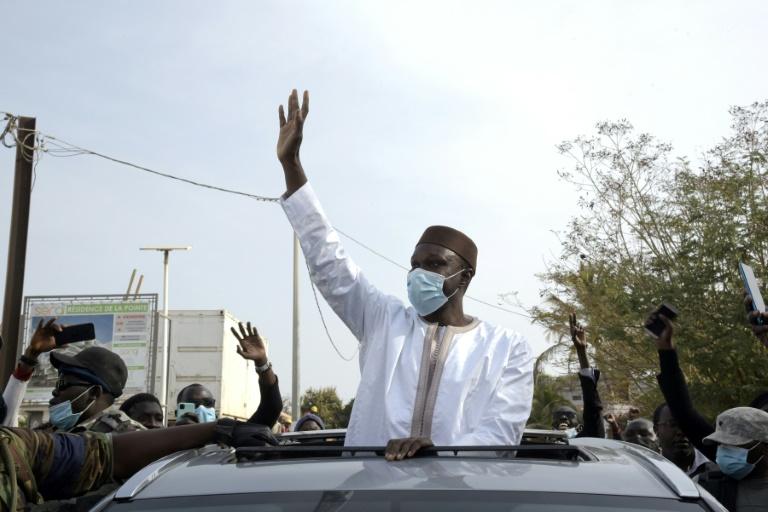 Ousmane Sonko, figure de l'opposition au Sénégal salue ses partisans le 3 mars 2021 à Dakar, sur le chemin vers le palais de justice, où il doit être interrogé pour des accusations de viols
