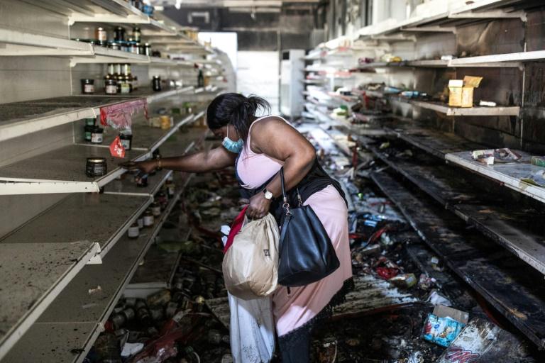Une femme s'empare de produits dans un magazin Auchan incendié et pillé à Dakar, le 6 mars 2021.