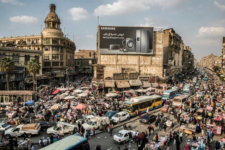 Des véhicules coincés dans un embouteillage au milieu des vendeurs ambulants dans un quartier du Caire le 22 février 2021