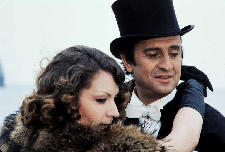 """Les acteur et actrice français Georges Descrières (d) et Claude Degliame lors d'un tournage de la série """"Arsène Lupin"""" sur une plage d'Etretat (Seine-Maritime), le 4 mai 1973"""