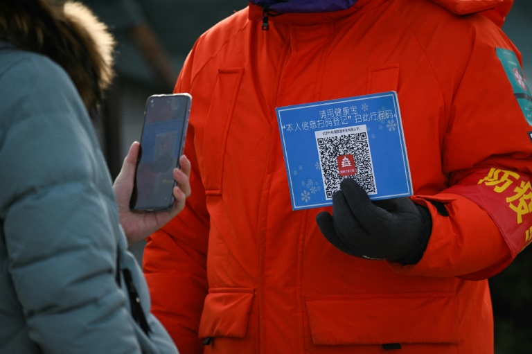 Une femme s'enregistre en scannant un QR code avant d'entrer dans une patinoire de Pékin, le 12 janvier 2021