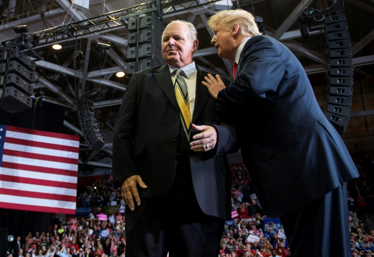 (FILES) In this file photo taken on November 05, 2018, Then-president Donald Trump speaks to radio host Rush Limbaugh at a Make America Great Again rally in 2018