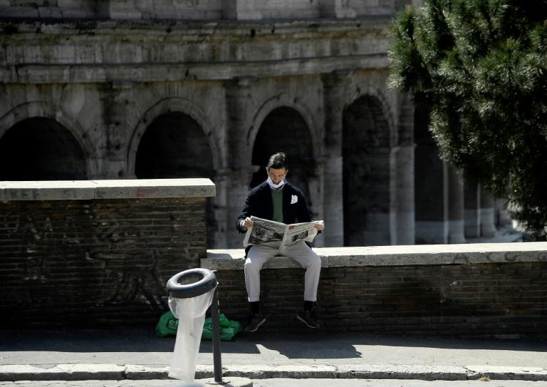 Un homme lit un journal devant le Colisée à Rome le 16 avril 2020. Google a signé mercredi des accords de licence visant à rémunérer la presse italienne.