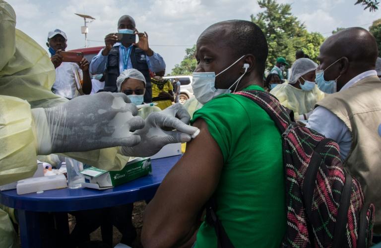 Un membre du personnel du ministère guinéen de la Santé administre à un patient un vaccin anti-Ebola à Gueckedou, le 23 février 2021