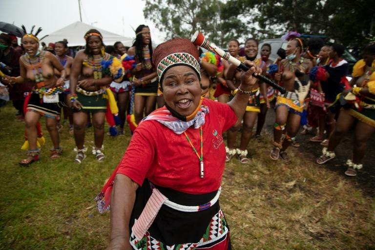 Une femme zouloue dance au milieu de jeunes filles près de l'entrée du palais du défunt roi Goodwill Zwelithini, le 17 mars 2021, à Nongoma, en Afrique du Sud