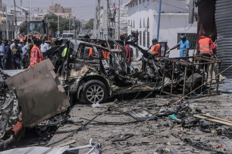 Des membres des services de secours près de la carcasse d'une voiture piégée qui a explosé, le 13 février 2021 à Mogadiscio, en Somalie