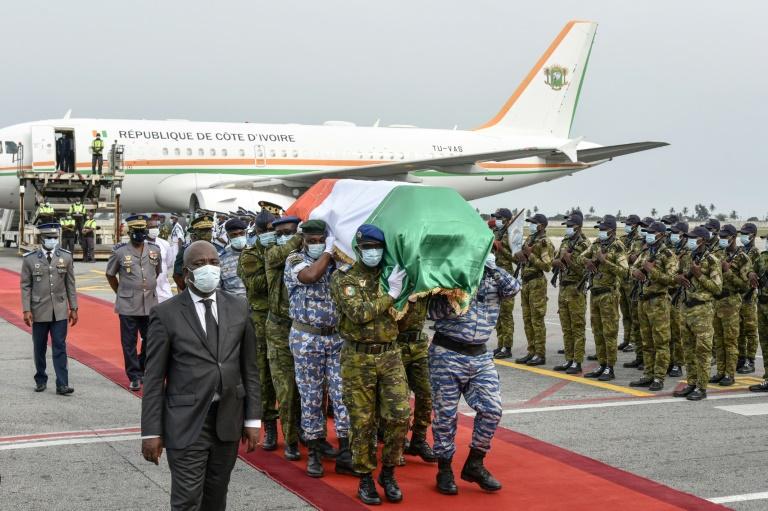 Des soldats ivoiriens portent le cercueil d'Hamed Bakayoko, à l'aéroport d'Abidjan, le 13 mars 2021.